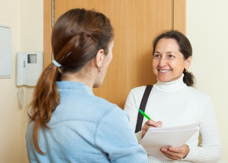 social worker:  woman filling questionnaire for mature employee with paper at door