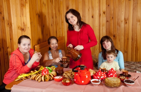 banket: Women  with child drinks tea and eats pancake  in home Stock Photo