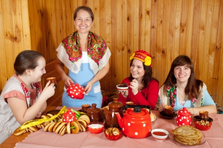 banket: Women in traditional clothes celebrating Shrovetide and eats pancake