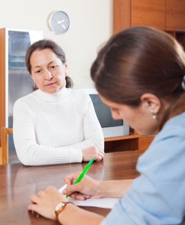 Mature woman filling questionnaire for employee with paper photo
