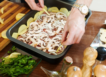 roasting pan: Stages of cooking french-style meat. Adding portatoes in roasting pan Stock Photo