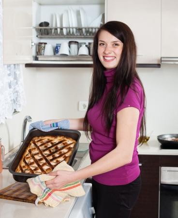 pesce cotto: Ragazza felice con cotto torta di pesce nella cucina di casa