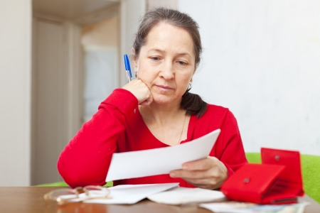 lamentable: serious mature woman reads payment documents at home