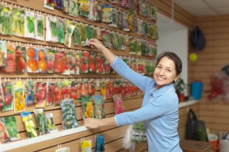 Smiling mature woman chooses packaged seeds at store for gardener photo