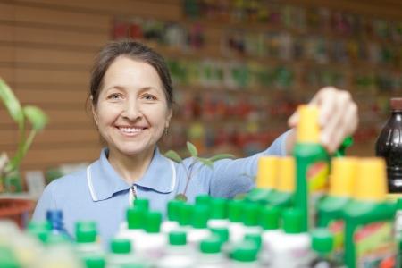 Happy mature  woman chooses  liquid fertilizer at store for gardeners Stock Photo - 25275000