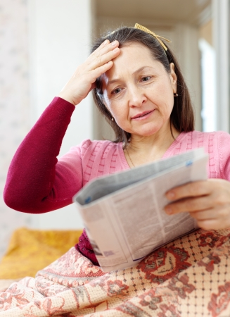 hardships:  mature woman having grief  after readed news in newspaper Stock Photo