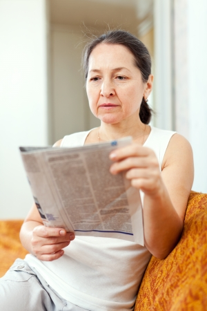 serious and wistful mature woman reads newspaper at home
