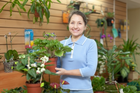 Happy mature woman with primula surrounded by different flowers in flower store photo