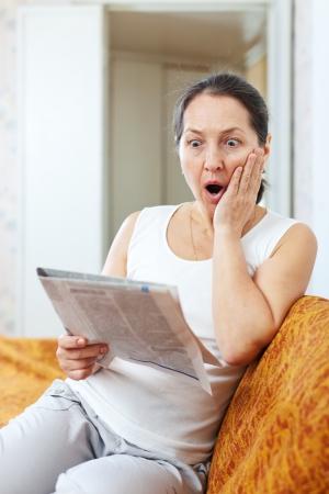 decide: Mujer madura sorprendido mira peri�dico en su casa Foto de archivo