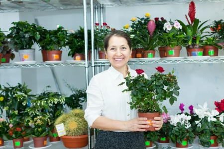 Happy mature woman chooses roses at flower store photo