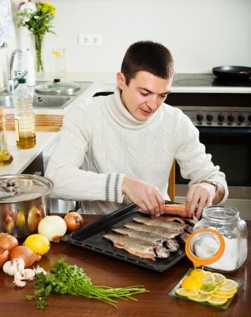 roasting pan:  guy cooking raw fish  in roasting pan at home kitchen