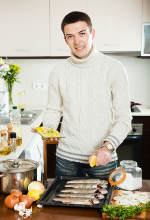 Handsome man cooking trout fish with lemon in baking sheet at home  photo
