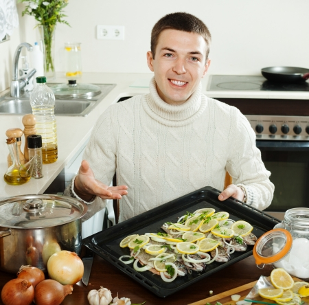 Handsome man with raw fish on roasting pan at  kitchen photo