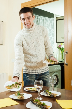 brook trout: Handsome man serving cooked fish on the table at home   Stock Photo