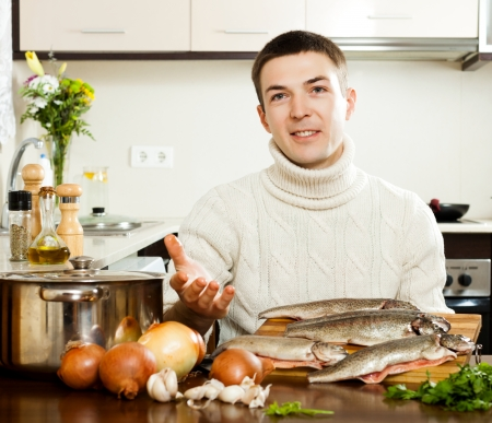 man with raw trout fish at home kitchen photo