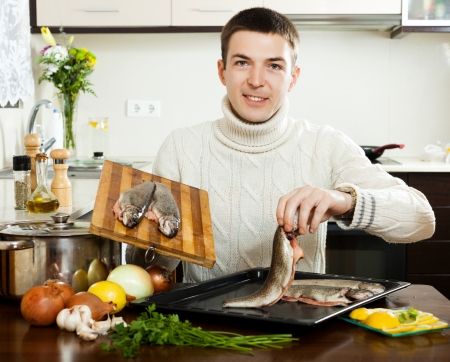 Smiling guy cooking  fish  in frying pan at  kitchen photo