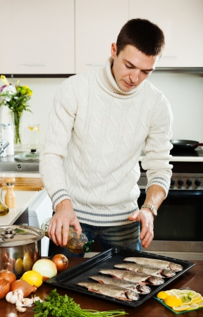 Handsome guy pouring oil in raw fish on roasting pan at  kitchen  photo