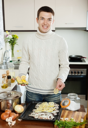 brook trout: Handsome man cooking raw fish with lemon and onion in baking shee