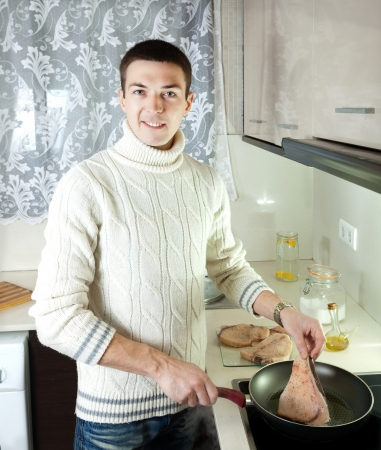 Handsome man frying raw steak of fish at home kitchen photo
