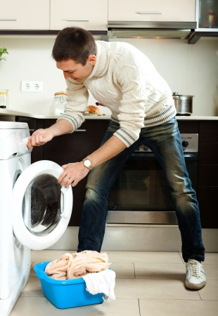 Handsome man loading clothes into the washing machine  in home photo