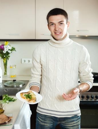 pesce cotto: sorridente ragazzo con cotto bistecca di pesce sulla piastra a casa cucina