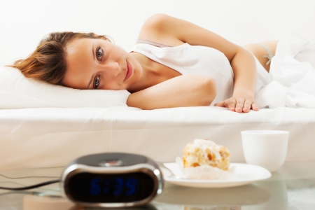 Long-haired woman having sweet cake and cafe at bed in morning photo