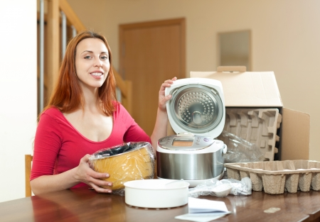 Woman with electric crock pot in her kitchen in her living room  photo