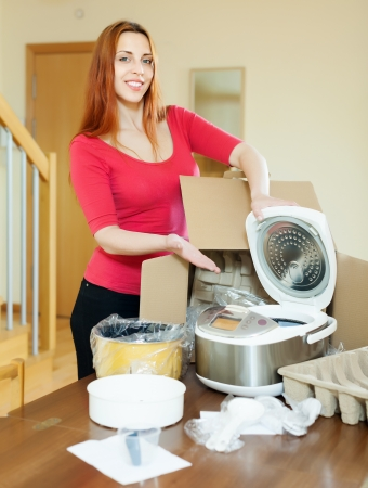 Happy young housewife unpacking new multicooker in home interior photo