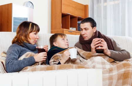 freezing parents and teenage son warming near warm heater in home