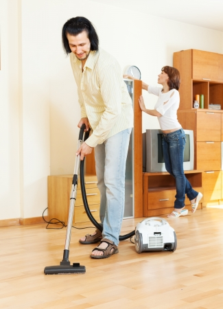 middle-aged couple doing housework together in home photo