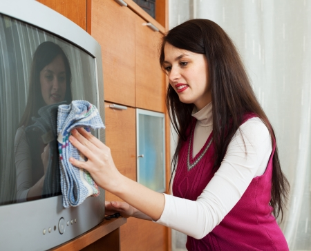 televisor:  woman wiping the dust on TV in living room at home