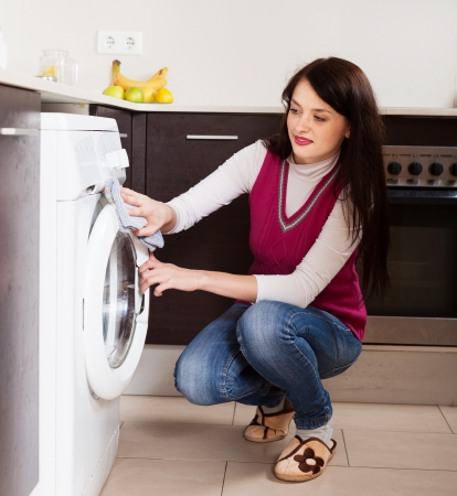 woman cleaning washing machine at home kitchen photo