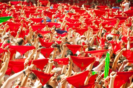 mob: PAMPLONA, NAVARRE - JULY 6: Cheering people with red shawl in July 6, 2013 in Pamplona, Navarre. Ð¡rowd waiting the opening of San Fermin festival