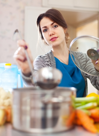 young woman cooking veggie soup with laddle in  kitchen  at home photo