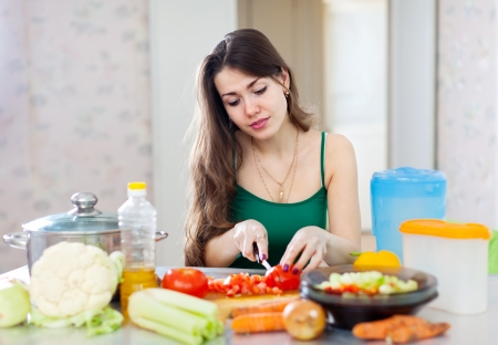 beautiful woman cooking vegetarian salad in  kitchen  photo
