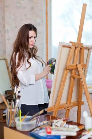 Donna dai capelli lunghi dipinge con colori ad olio su cavalletto in interni