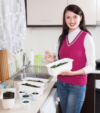 Happy woman with  sprouts at home kitchen photo