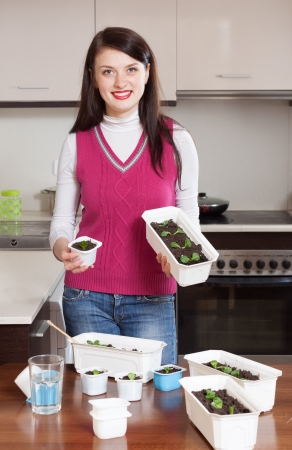 Happy brunette woman with  sprouts at home kitchen photo