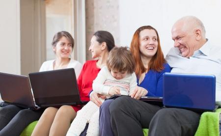 Happy family enjoys on sofa in livingroom with few laptops photo