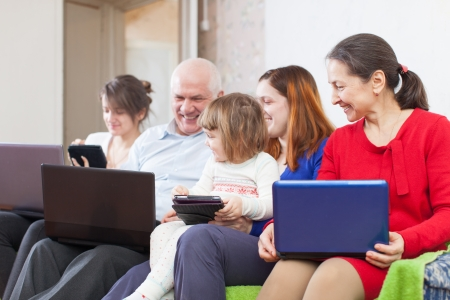 family of three generations on sofa in livingroom  with laptops  at home photo