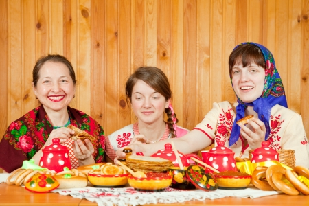 banket: Women in traditional  clothes eating pancake   during  Pancake Week