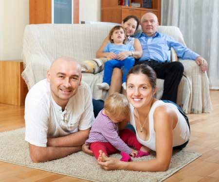 multigeneration: Portrait of happy multigeneration family with little children at floor in home
