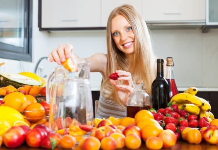 Happy woman making fruits beverages with wine  photo
