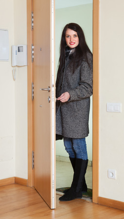 Woman in coat unlocking the door in home photo