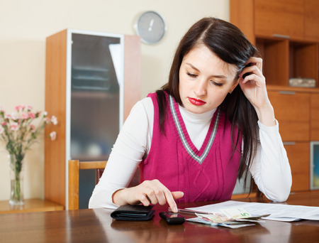 utility payments: serious housewife filling in utility payments bills at  home Stock Photo
