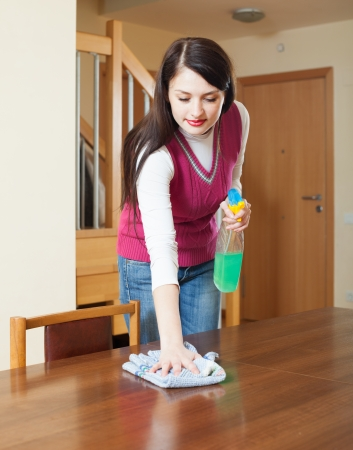 long-haired girl  dusting table with detergent polish at home photo