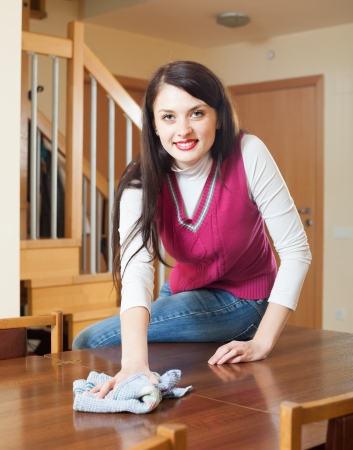 brunette woman dusting  table at home photo