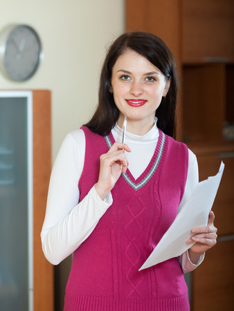 home office interior: Smiling  woman with financial documents at home or office interior