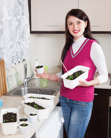 Happy female gardener with various seedlings at home photo