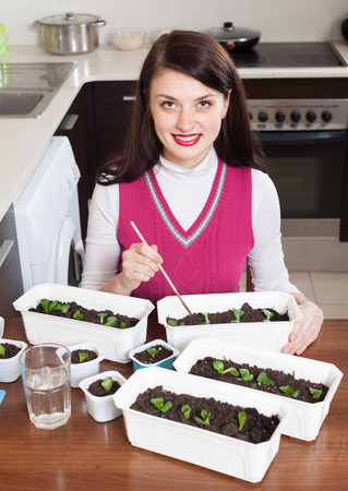 brunette girl working with  seedlings at table in home kitchen photo